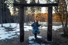 摇摆在摇摆的愉快的少妇有乐趣和微笑在公园在晴朗的冬日 一个人 免版税库存图片