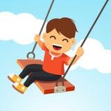 摇摆在摇摆的愉快的微笑的男孩孩子 图库摄影