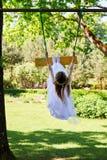 摇摆在摇摆的白色礼服的女孩 免版税库存图片