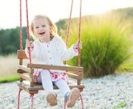 摇摆在操场的小女孩 童年,自由,愉快的夏天概念 库存照片