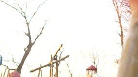 摇摆在操场的摇摆的可爱的青少年的女孩在寒假期间 女孩戴一个桃红色被编织的帽子 股票视频