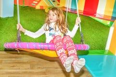 摇摆在操场的摇摆的小女孩 免版税库存图片