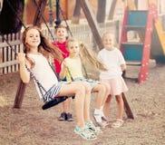 摇摆在操场的笑的女孩和男孩 库存图片