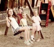 摇摆在操场的笑的女孩和男孩 免版税库存图片