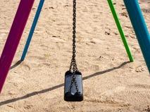 摇摆在有垂悬在链子的黑塑料位子的含沙儿童` s操场 免版税库存照片