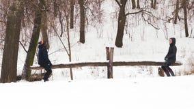 摇摆在木摇摆的慢动作、男孩和女孩在冬天在森林里 影视素材