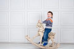 摇摆在木马的小男孩 牛仔裤和毛线衣的滑稽的三岁的男孩在白色背景 无忧无虑的童年 免版税库存图片