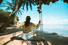 摇摆在热带海滩的摇篮的女性游人 免版税图库摄影