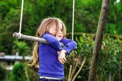 摇摆在跷跷板的逗人喜爱的小女孩 免版税库存照片