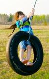 摇摆在轮胎摇摆的小女孩 免版税图库摄影