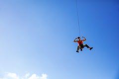 摇摆在绳索和屈曲肌肉的攀岩运动员 免版税库存照片