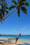 摇摆在绳索摇摆的少妇在Pangaimotu海岛在T附近 免版税图库摄影