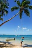 摇摆在绳索摇摆的少妇在Pangaimotu海岛在T附近 库存照片