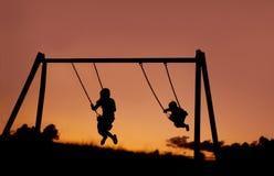 摇摆外面在日落的两个孩子剪影。 库存图片