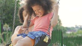 摇摆她心爱的女儿的俏丽的母亲在后院,家庭幸福