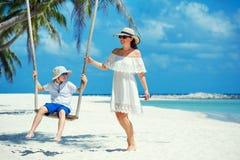 摇摆她的一个热带海滩的,酸值Phangan海岛的年轻美丽的妇女儿子 泰国 免版税库存图片