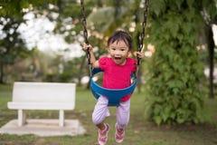 摇摆的亚裔中国两岁的女孩在操场 免版税库存图片