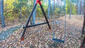 摇摆的关闭在秋天,摇摆在风的被放弃的空的摇摆在儿童操场户外-在公园秋天晴朗的d 股票视频