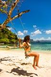 摇摆的卷曲女孩在Cudugnon洞,巴拉望岛,菲律宾附近的海滩 免版税库存照片