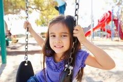 摇摆的女孩在公园 免版税库存图片