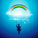 摇摆的小女孩在彩虹之下 免版税库存照片