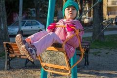 摇摆的小女孩在操场 免版税库存照片