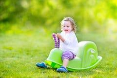 摇摆的小孩女孩在一个晴朗的庭院里 免版税库存照片