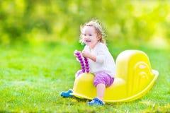 摇摆的小孩女孩在一个晴朗的庭院里 库存照片