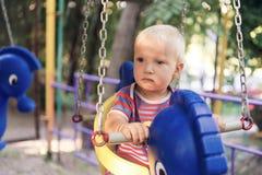 摇摆的小白肤金发的男孩在夏天公园 免版税库存照片
