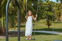 摇摆的快乐的微笑的小女孩在热带庭院里 免版税库存图片