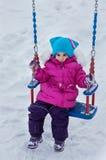 摇摆的愉快的儿童女孩在日落冬天 使用在冬天步行的小孩本质上 图库摄影