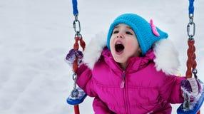 摇摆的愉快的儿童女孩在日落冬天 使用在冬天步行的小孩本质上 免版税库存图片