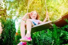 摇摆的愉快的儿童女孩在晴朗的夏天庭院里 图库摄影