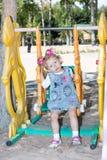 摇摆的愉快的可爱的儿童女孩在幼儿园蒙台梭利附近的操场在夏天 免版税库存照片