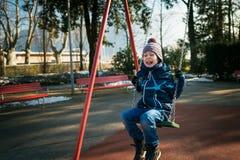 摇摆的愉快的小男孩在美好的冬日 免版税库存图片