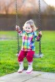 摇摆的愉快的笑的女婴在庭院里 免版税库存图片