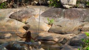 摇摆的无忧无虑的妇女在密林森林后面视图 摇摆在热带森林山的摇摆的少妇  影视素材