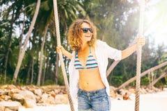 摇摆的美丽的年轻卷曲滑稽的女孩在一个热带海滩, 免版税库存照片