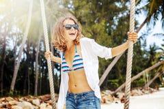 摇摆的美丽的年轻卷曲滑稽的女孩在一个热带海滩, 图库摄影