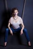 摇摆的美丽的年轻性感的女孩从绳索在黑背景的演播室在牛仔裤和明亮的构成 免版税库存图片