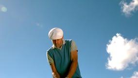 摇摆他的俱乐部的英俊的高尔夫球运动员 影视素材