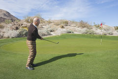 摇摆他的俱乐部的资深男性高尔夫球运动员全长侧视图在高尔夫球场 免版税库存照片