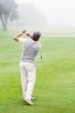 摇摆他的在路线的高尔夫球运动员俱乐部 免版税图库摄影