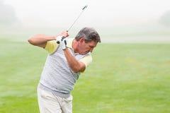 摇摆他的在路线的高尔夫球运动员俱乐部 免版税库存照片