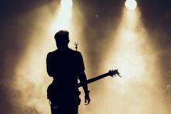 摇滚乐队在阶段执行 吉他弹奏者独奏使用 吉他演奏员剪影行动的对在音乐会人群前面的阶段 关闭 库存照片