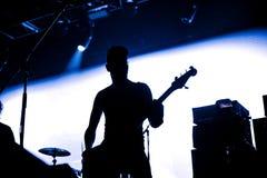 摇滚乐队在阶段执行 吉他弹奏者独奏使用 吉他演奏员剪影行动的对在音乐会人群前面的阶段 关闭 库存图片