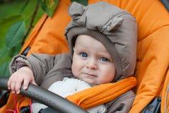摇篮车的小男婴在冬天穿衣 免版税库存照片