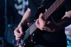 摇滚乐背景,低音吉他球员,与软的选择聚焦的特写镜头照片 免版税库存照片