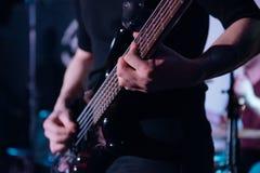 摇滚乐背景,低音吉他球员,与软的选择聚焦的特写镜头照片 图库摄影