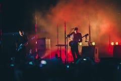 摇滚乐队在阶段执行 吉他弹奏者独奏使用 吉他演奏员剪影行动的对在音乐会人群前面的阶段 免版税库存照片